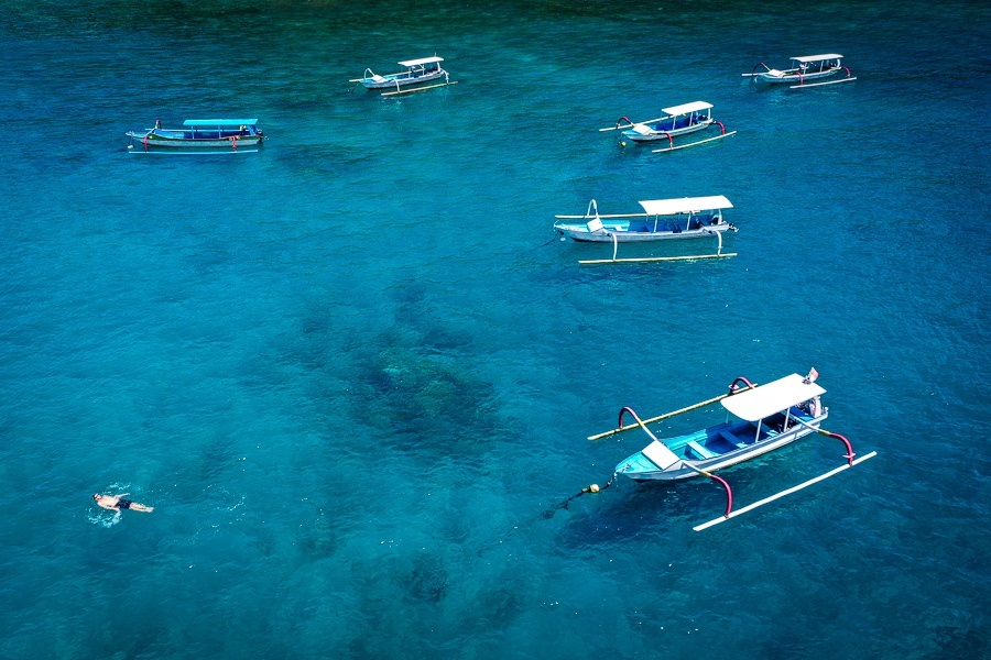 Drone view of boats and swimmer floating at Crystal Bay in Nusa Penida, Bali