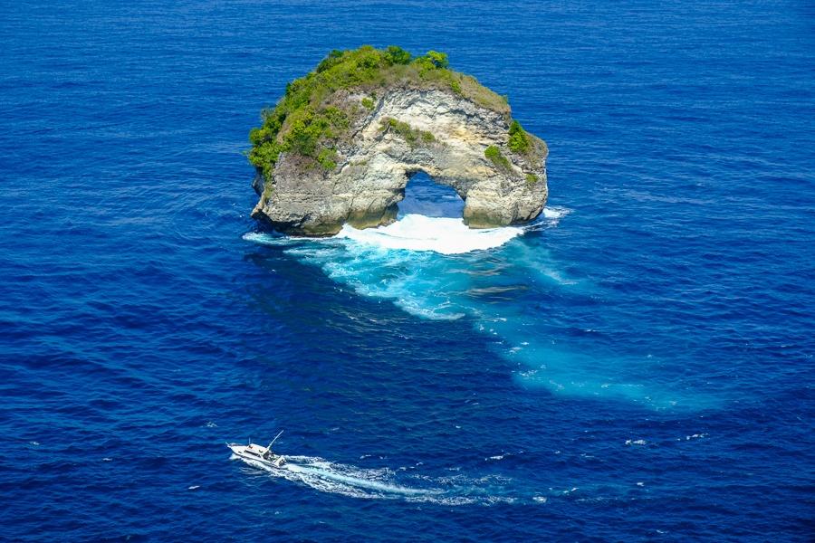 Speedboat driving near the Banah rock at Banah Cliff Point in Nusa Penida, Bali