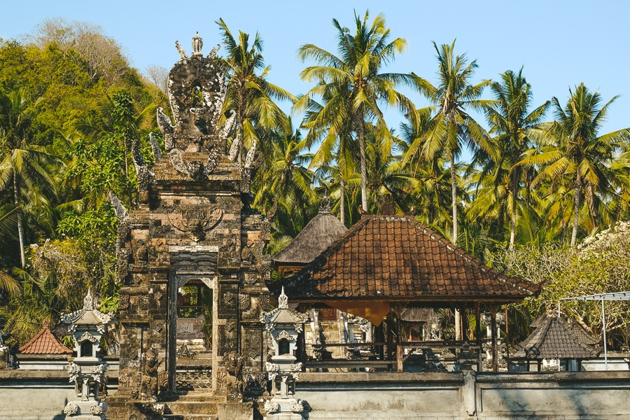 Palm trees and Balinese Hindu temple at Crystal Bay in Nusa Penida, Bali