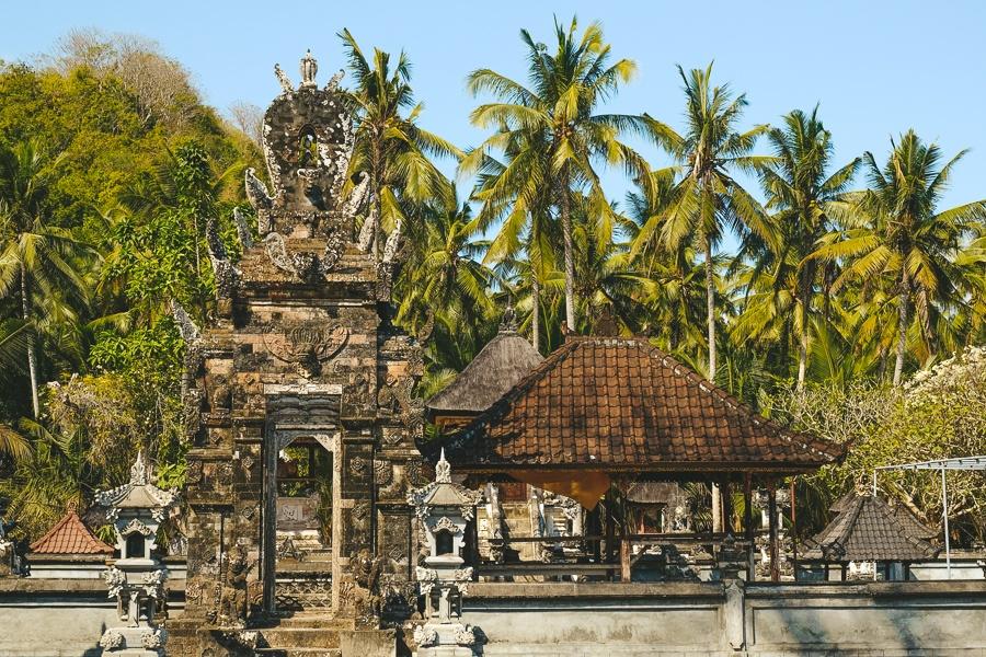 Palm trees and Balinese Hindu temple at Crystal Bay in Nusa Penida, Bali