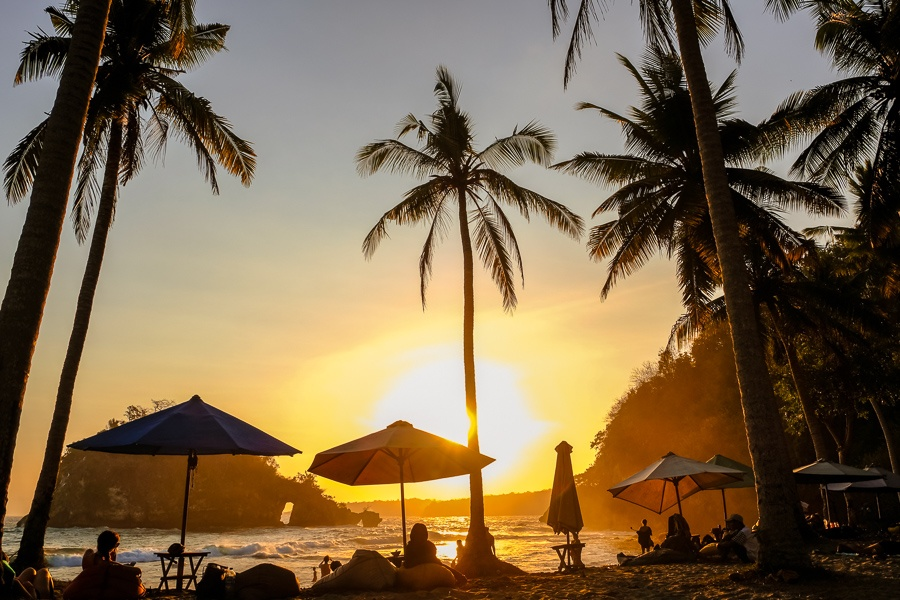 Tourists with the sunset and palm trees at Crystal Bay in Nusa Penida, Bali