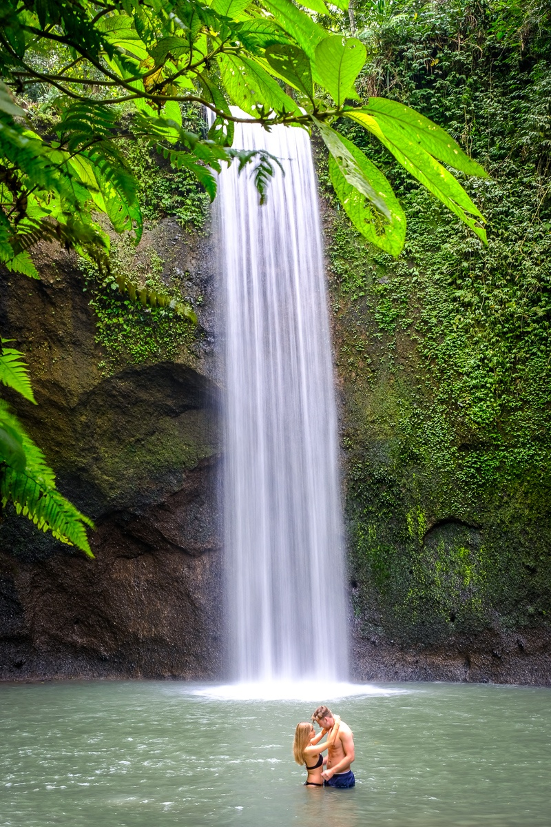 Tourist couple posing at Tibumana Waterfall in Bali