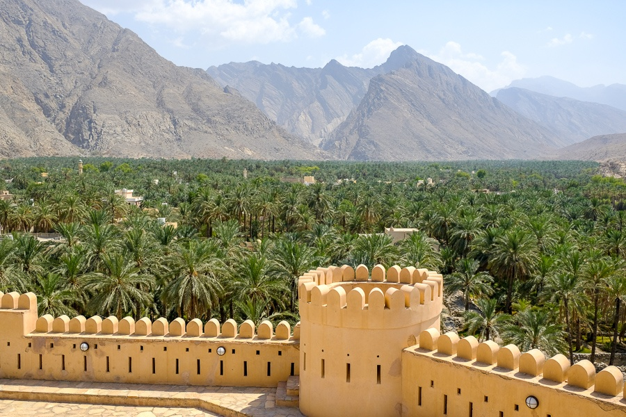 Wall and distant palm trees and mountains near Nakhal Fort in Oman