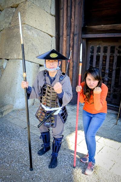 My woman posing with the fun play samurai guard at Himeji Castle in Japan