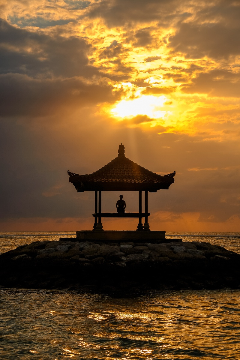 Woman sitting in a pagoda during sunrise at Sanur Beach in Bali