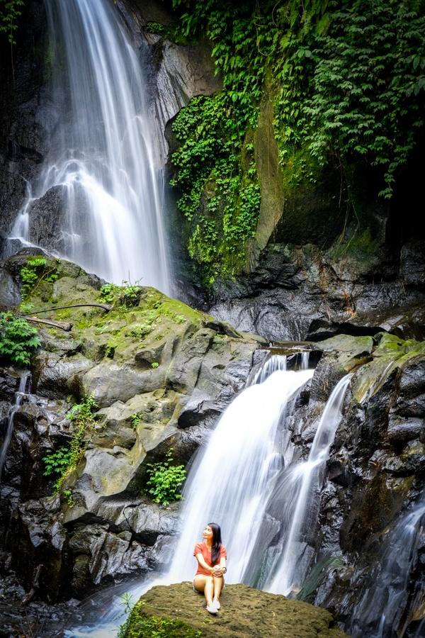 My woman sitting at Pengibul Waterfall in Bali