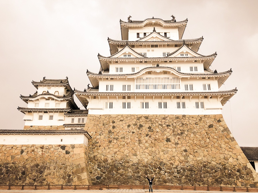 Tiny travel guy posing with the huge Himeji Castle in Japan