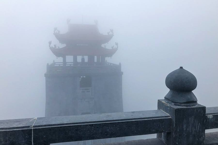 Very foggy pagoda and railing at Fansipan mountain in Sapa, Vietnam