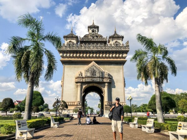 Travel guy standing in front of the Patuxai Victory Monument in Vientiane, Laos