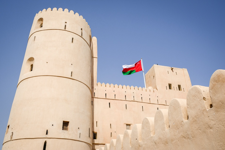 Fort walls and Omani flag at An Naman Castle in Oman
