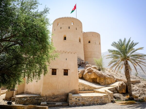 Castle towers and Omani flag at Rustaq Fort in Oman