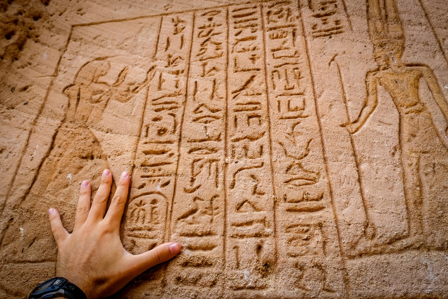 Hand holding ancient Egyptian inscriptions
