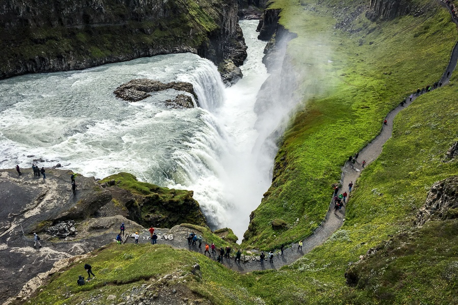 Tourists walking on a path near Gullfoss Waterfall in Iceland