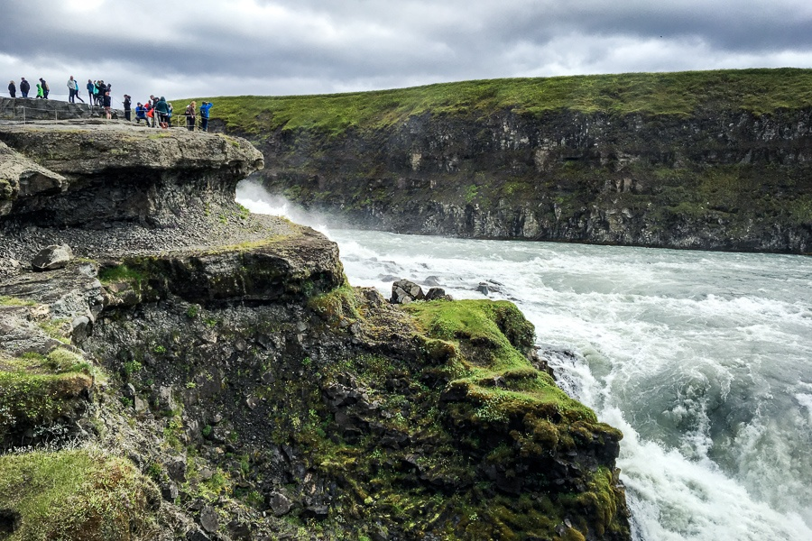 Tourists standing near the edge of the Gullfoss Waterfall in Iceland