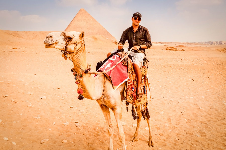 Travel guy riding a camel at the Great Pyramids of Giza in Egypt