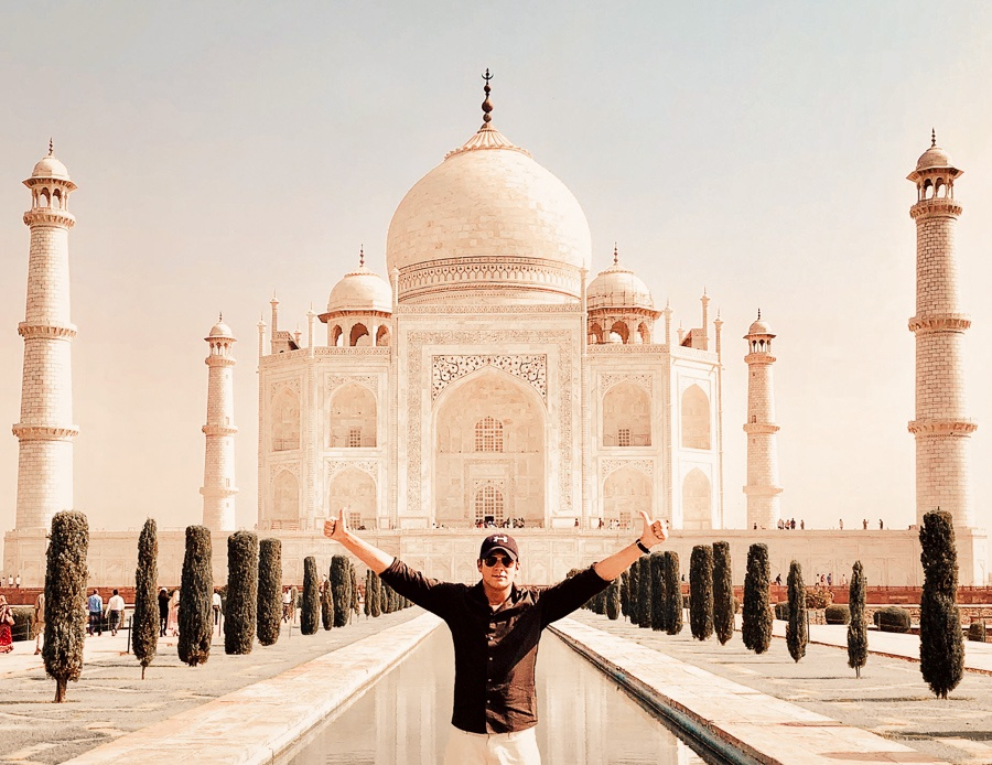 Travel guy posing at the Taj Mahal in Agra, India