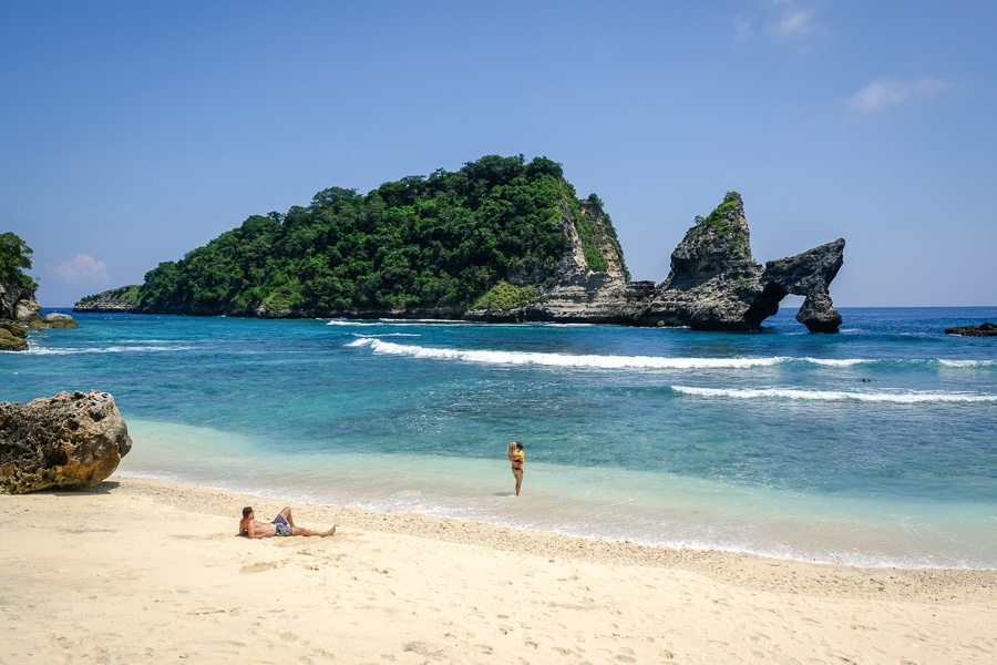 Tourist couple relaxing with their kid on the sand at Atuh Beach in Nusa Penida, Bali