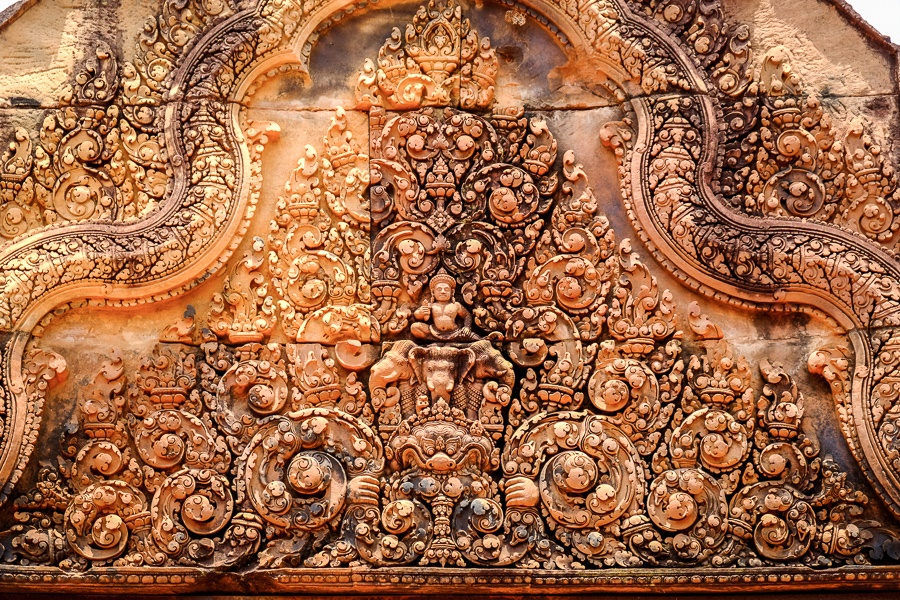 Intricate Hindu carvings in an orange stone wall at Banteay Srei