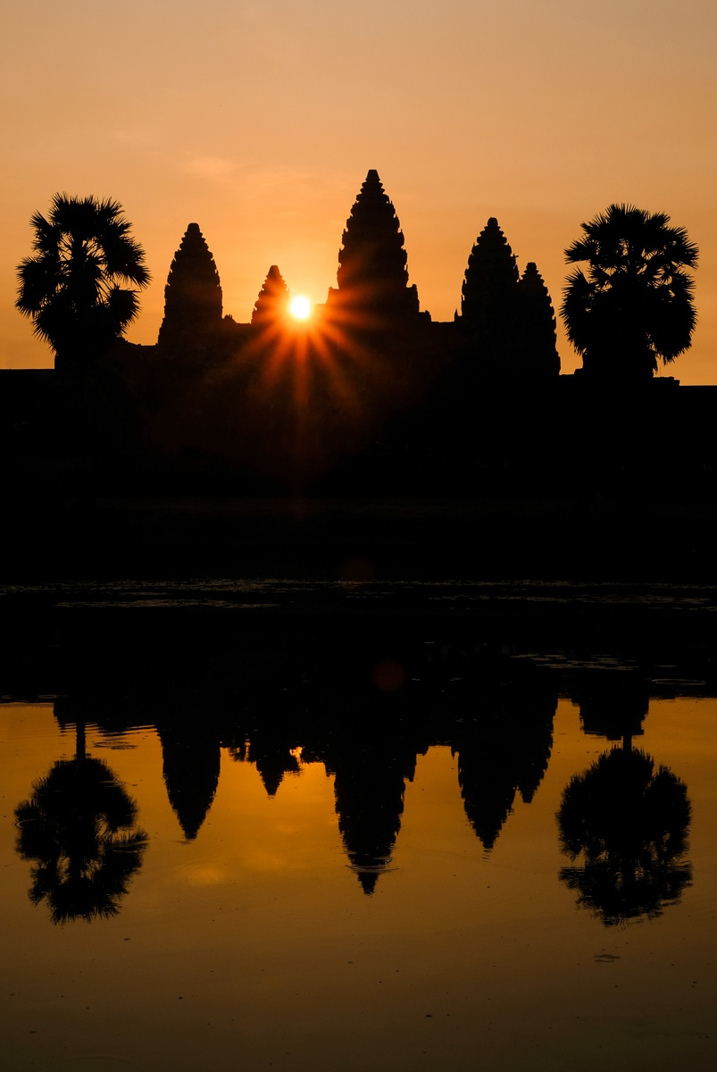 Colorful sunrise behind the outline of Angkor Wat temple in Cambodia