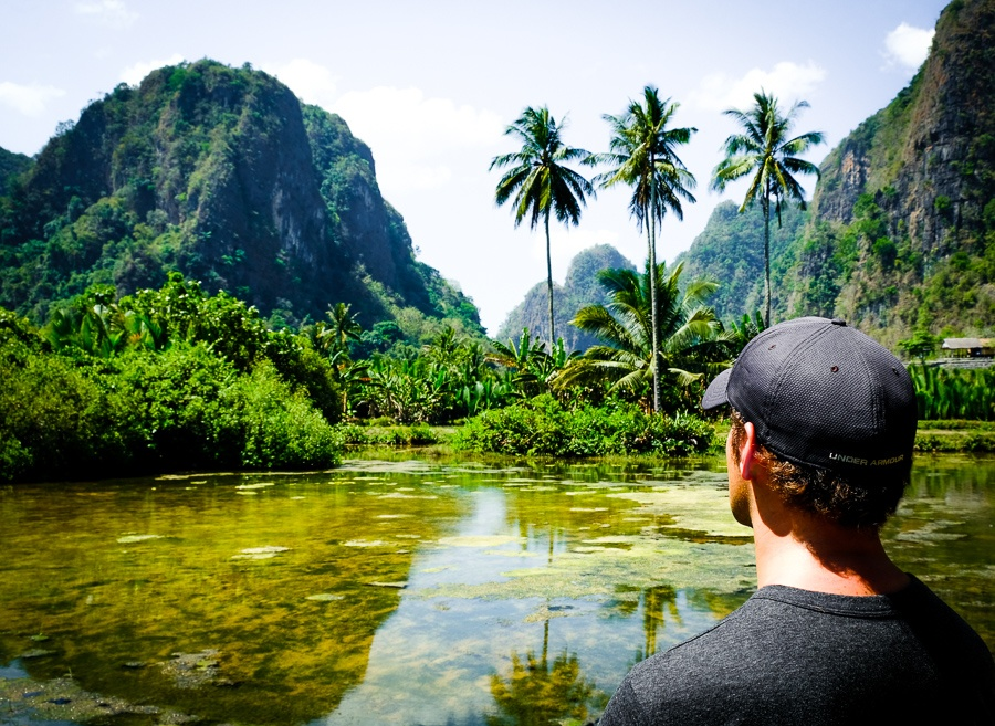 Travel guy at the Rammang Rammang Maros mountains and pond in Sulawesi Indonesia