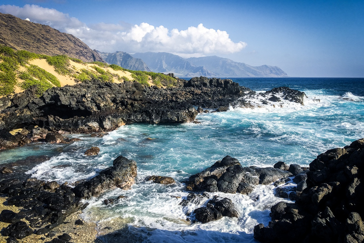 Waves and mountains on the coastline at Ka'ena Point in Oahu, Hawaii