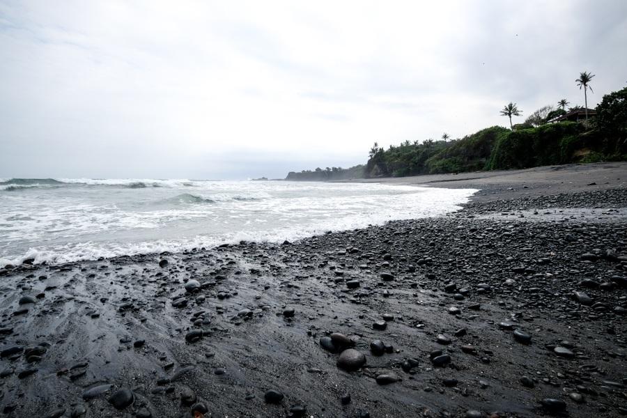 Black sand rocks and waves at Balian Beach in Bali