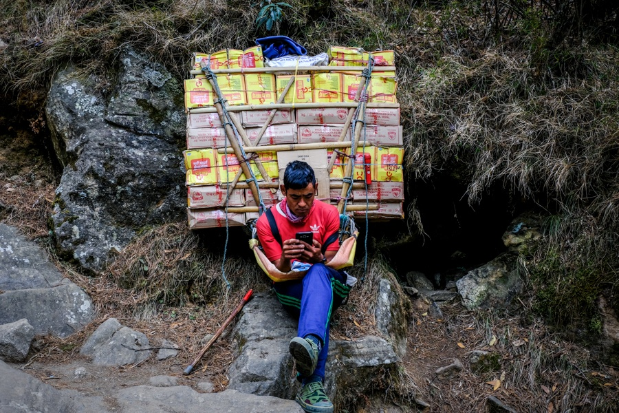 Porter with a huge pack on the EBC trek in Nepal