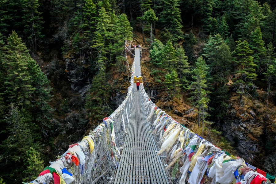 Porter walking on a steep mountain bridge on the EBC trek in Nepal