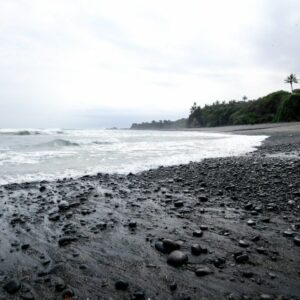 Black sand rocks and waves at Balian Beach in Bali