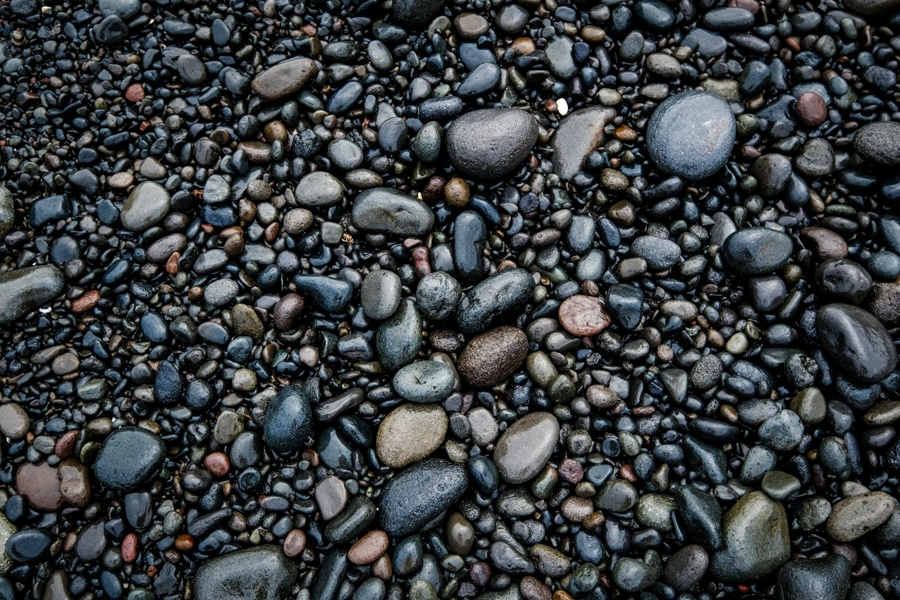 Black sand rocks and smooth stones at Balian Beach in Bali