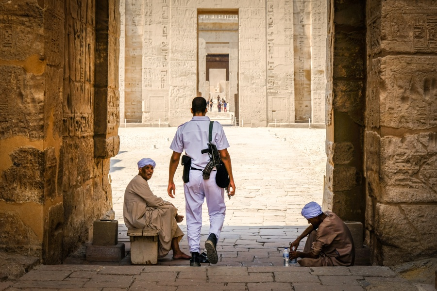 Security guard policeman and beggars at Medinet Habu Temple in Egypt