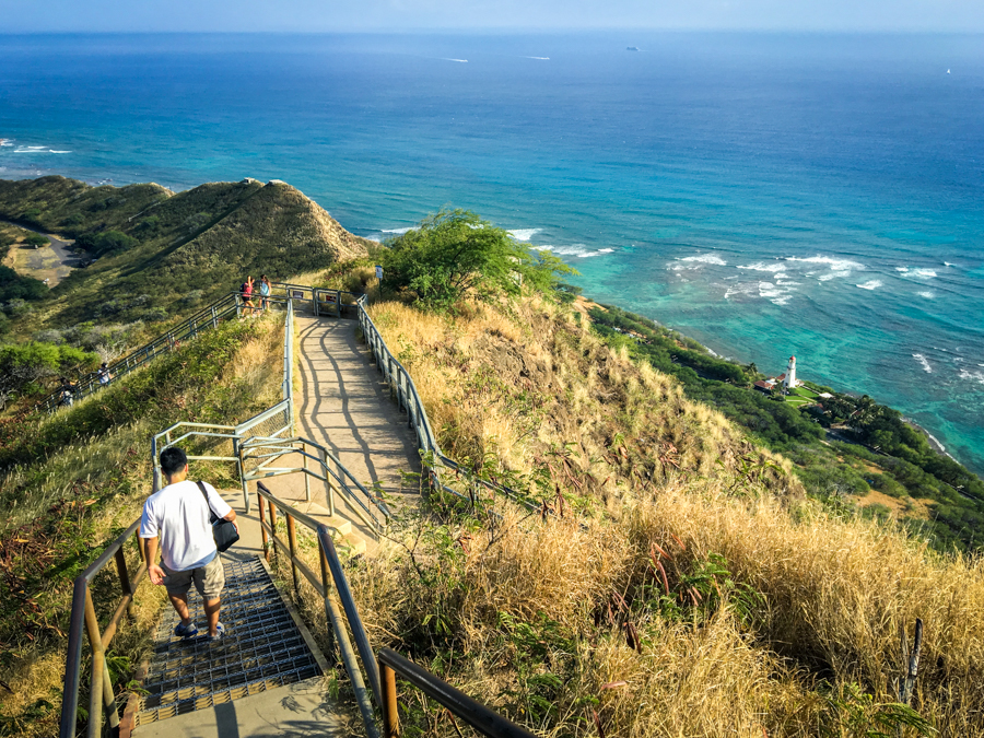 Hiker walking down the steps at Diamond Head trail, with ocean views in the distance